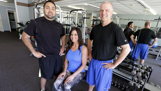 Today: Ricardo Arguello (left) and Mike Sherry (right) pose with personal trainer Maria Munoz at Personal Fitness Trainers and Wellness Studio in Appleton at the end of their 48-week fitness program.