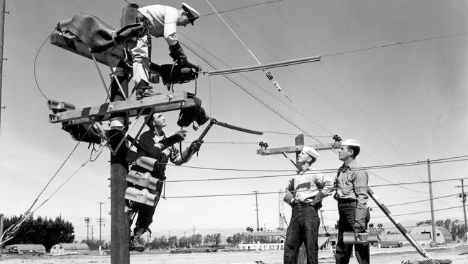 Construction electricians make up part of the Seabee force. In this 1951 photo, a chief electrician demonstrates an electrical installation to new Seabees.