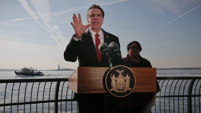 New York Gov. Andrew Cuomo, center, holds a press conference with the Statue of Liberty in the distance behind him, Sunday Jan. 21, 2018, in New York. Cuomo says the statue and Ellis Island will be open for visitors on Monday, with New York state picking up the tab for federal workers.  The two sites have been closed due to the federal government shutdown.