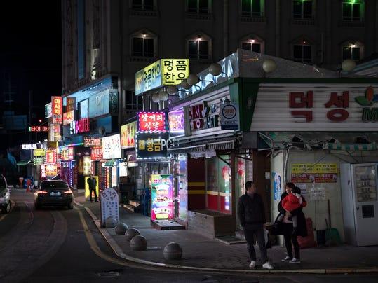 A family waits at a taxi stop in the town of Sabuk, Jeongseon county, South Korea, Thursday, Feb. 15, 2018. (AP Photo/Felipe Dana)