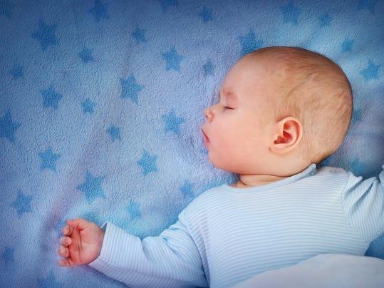 three month old baby sleeping on blue blanket