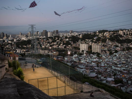 Kites fly over a soccer field at the Sao Carlos slum in Rio de Janeiro, Brazil, Monday, May 12, 2014. (AP Photo/Felipe Dana)