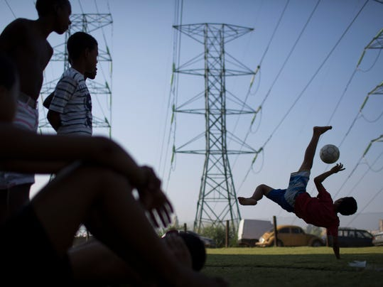 Boys watch as another boy practices his soccer bicycle kicks at a Rio de Janeiro slum, Brazi, Monday, June 9, 2014. The 2014 Word Cup soccer tournament is set to begin in just a few days, with Brazil and Croatia playing in the opening match on June 12. (AP Photo/Felipe Dana)