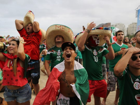 In this Friday, June 13, 2014 photo, Mexico soccer fan Jose Reyna, center, reacts as he watches his team's World Cup match with Cameroon inside the FIFA Fan Fest area on Copacabana beach in Rio de Janeiro, Brazil. Mexico won 1-0. (AP Photo/Leo Correa)