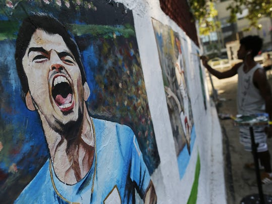 A mural of Uruguay's soccer striker Luis Suarez covers a wall as artist Marcos Jambeiro paints other players at Copacabana beach in Rio de Janeiro, Brazil, Thursday, June 26, 2014. FIFA banned Suarez from all football activities for four months on Thursday for biting an opponent at the World Cup, a punishment that rules him out of the rest of the tournament. (AP Photo/Leo Correa)