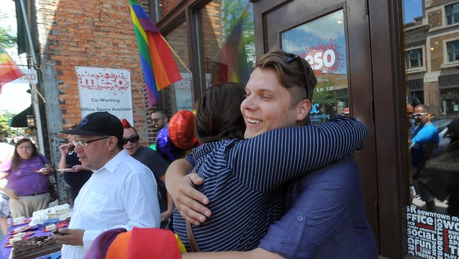 Thomas Christiansen is embraced by friend Amy Wentworth in front of Meso in downtown Sioux Falls, on Friday. The ACLU and Center for Equality held a celebration in honor of the Supreme Court's rule in favor of same-sex marriage nationwide.