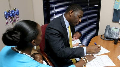 Tallahassee City Commissioner Andrew Gillum holds his twin son Jackson while files his paperwork to get on the ballot to run for mayor of Tallahassee. His wife, R. Jai holds daughter Caroline.