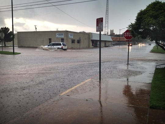 Water rushes over curbs and through the streets in downtown Wichita Falls on May 7, 2015. A strong thunderstorm moved through Wichita Falls and North Texas on that day, the beginning of historic rainfall in the area that would lift the region out of a drought.