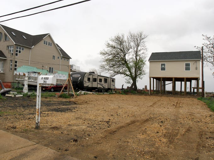 Pictured are 735 Front Street, which is a completed home, 737 Front Street, which is a lot with a boat, car and trailer, and 741 Front Street, which appears to be a raised new construction, in Union Beach, NJ Friday May 16, 2014.