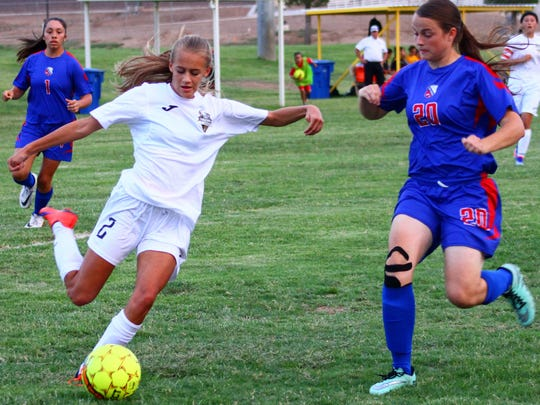 Alamogordo's Sheyenne Drake passes a ball while being challenged by Las Cruces' Jamie Cummings on Tuesday evening.