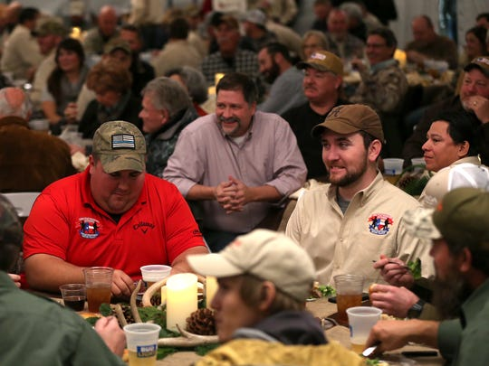 Two dozen veterans and active duty service members eat dinner at a banquet in their honor with over 200 guests as part of the Lone Star Warriors Outdoors deer hunt they will be participating in over the weekend.