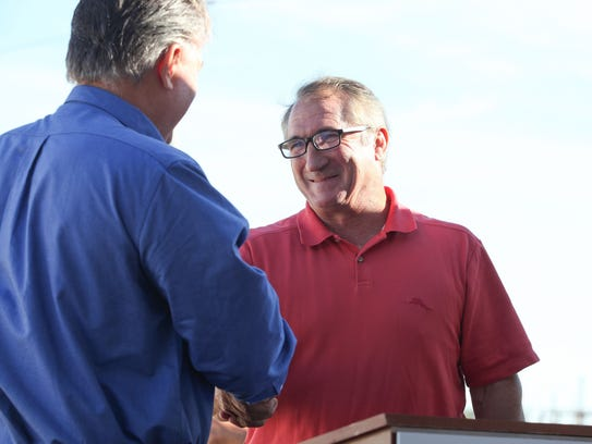 Mike Abatti, right, shakes hands with then-Imperial Irrigation District board member Matt Dessert, a longtime friend of his, at an event in El Centro on Oct. 26, 2016.