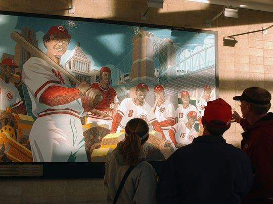 """Fans look over a mosaic of the 1975 Cincinnati Reds """"Great Eight"""" in the mezzanine of Great American Ball Park. The 1976 Reds also won the World Series and started the postseason with a seven-game winning streak."""