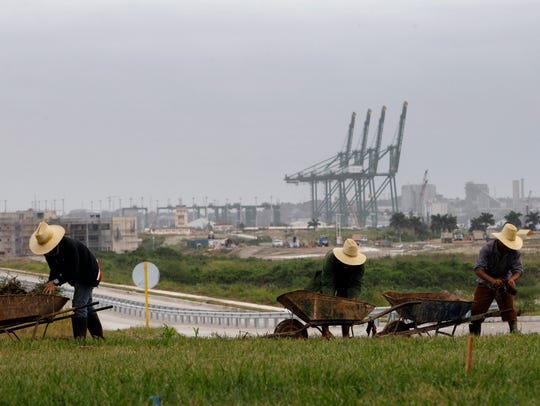 Workers landscape the area near a port under construction