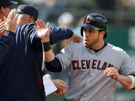 Cleveland Indians second baseman Jason Kipnis is congratulated after scoring against the Oakland Athletics in the ninth inning of a baseball game Wednesday, April 2, 2014, in Oakland, Calif. Kipnis scored on a single by Carlos Santana. (AP Photo/Ben Margot)