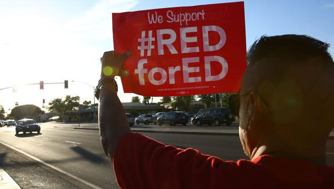 Arizona teachers protest along Baseline Road on April 25, 2018, in Mesa on the eve of a planned walkout on April 26, for higher pay and more education funding.