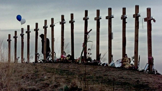 In this April 28, 1999, file photo, a woman stands among 15 crosses posted on a hill above Columbine High School in Littleton, Colo., in remembrance of the 15 people who died during a school shooting on April 20. In the decades since Columbine, there's been a growing call for media to avoid naming the gunmen in mass shootings.