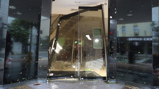 A door is seen blown in at a Regions Bank as Hurricane Irma passes through on Sept. 10, 2017 in Miami, Fla.