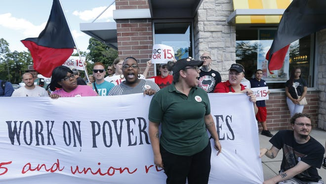 Alexsandra Candelaria, an employee at another McDonald's, stands in front of a banner during a rally in support of the $15 per hour minimum wage at the McDonald's on Culver Road and Main Street in Rochester.