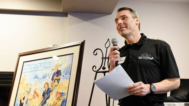 St. Cloud Rotary member Troy Fritz announced the bands Wednesday, April 6, for this years Summertime by George! concerts held at Lake George. The watercolor painting by artist Doug Lien, Sartell, (left) was also unveiled before the band announcement at the Regency Plaza.