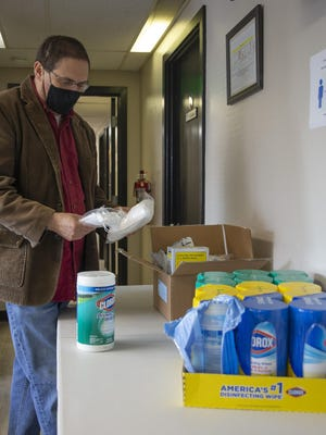 Centro Latino Americano execuive director David Saez looks at masks and disinfectant wipes May 22 to be used in the organization's offices once they re-open. The group, which supports the local Latino population, is one of several receiving grants from Lane County.  [Andy Nelson/The Register-Guard file] - registerguard.com