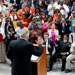 The crowd cheers during Gov. Terry McAuliffe's announcement on the restoration of rights to felons in Virginia at the Capitol in Richmond Va., Friday, April 22, 2016. More than 200,000 convicted felons will be able to cast ballots in the swing state of Virginia in November's election under a sweeping executive order by McAuliffe announced Friday that restores their rights to vote and run for office. (Mark Gormus /Richmond Times-Dispatch via AP) MANDATORY CREDIT
