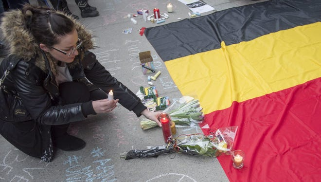 A woman places a candle next to a Belgian flag during a vigil on March 23 in Montreal.