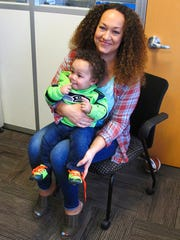 In this March 20, 2017 photo, Rachel Dolezal poses for a photo with her son, Langston in the bureau of the Associated Press in Spokane, Wash. Dolezal, who has legally changed her name to Nkechi Amare Diallo, rose to prominence as a black civil rights leader, but then lost her job when her parents exposed her as being white and is now struggling to make a living.