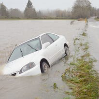 A car sits in a ditch after it swerved off a road flooded with high water in Mount Vernon, Wash., on Nov. 17, 2015.