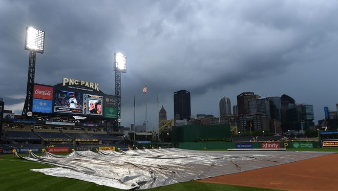 The PNC Park grounds crew removes the tarp from the field during a rain delay Wednesday night, but only temporarily.