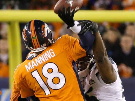 FILE - In this Feb. 2, 2014, file photo, Denver Broncos' Peyton Manning is hit by Seattle Seahawks' Cliff Avril as he throws an interception during the first half of the NFL Super Bowl XLVIII football game, in East Rutherford, N.J. Seattle defeated Denver 43-8. (AP Photo/Mark Humphrey, File)
