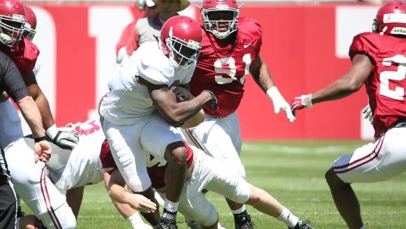 Bo Scarbrough (9) runs through the defense in Saturday's