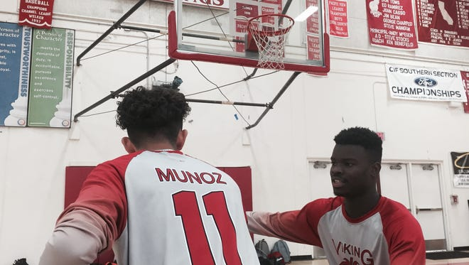 Hueneme's Javier Munoz, left, and Jalen Baker love the team's new shooting shirts that are made from material created from recycled water bottles.