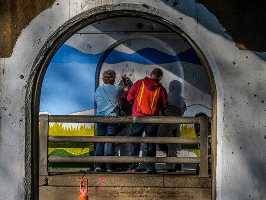 Volunteer painters work on a mural underneath the train