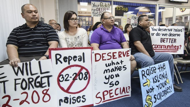 In this January 2015 file photo, protesters hold signs at public hearing at the Guam Legislature on Sen. Michael San Nicolas' bill to repeal pay raises for elected and appointed officials.