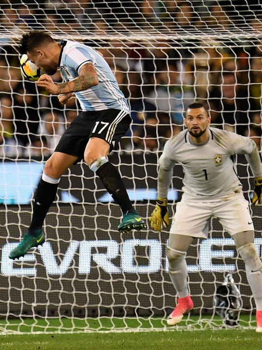 Nicolas Otamendi of Argentina, left, heads the ball as Brazil goalkeeper Weverton watches during their friendly soccer international at the Melbourne Cricket Ground in Melbourne, Australia, Friday, June 9, 2017. (Joe Castro/AAP Image via AP)