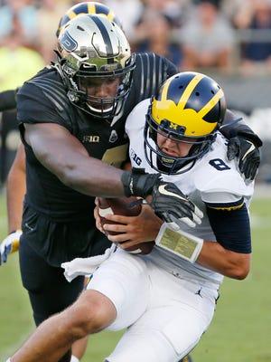 Michigan quarterback John O'Korn slips through the hands of Purdue linebacker Ja'Whaun Bentley in the second half.