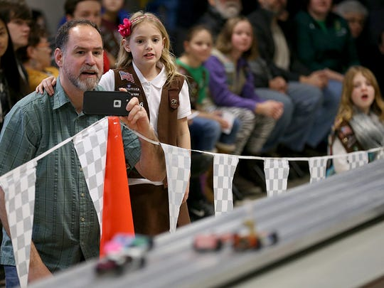 Evy Fafferty and her father, Jim, watch racing as the Irondequoit Girl Scouts held their first Pinewood Derby with help from Boy Scout Troop 203, who donated their time, equipment, and services to help run the event.