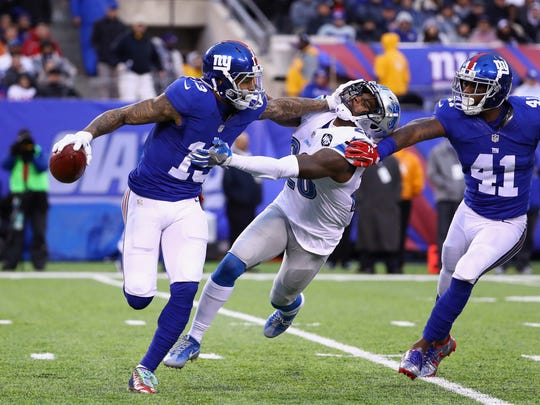 Giants receiver Odell Beckham carries the ball as he escapes a tackle from Lions safety Don Carey in the second half at MetLife Stadium on Dec. 18, 2016 in East Rutherford, N.J.