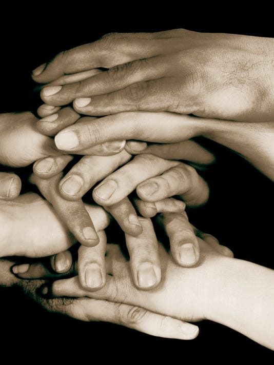 Hands stacked on top of one another on conference table
