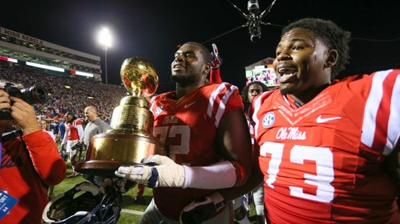 Ole Miss' Aaron Morris (72) and Rod Taylor (73) carry the Egg Bowl trophy after defeating MSU. Mississippi State played Ole Miss in a college football game on Saturday, Nov. 29, 2014 at Vaught-Hemingway  Stadium in Oxford, Miss. (Photo by Keith Warren)