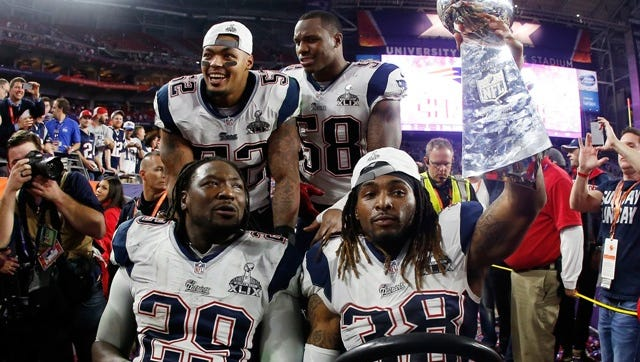 GLENDALE, AZ - FEBRUARY 01:  LeGarrette Blount #29,  Brandon Bolden #38,  Darius Fleming #58 and  Ryan Wendell #62 celebrate with the Vince Lombardi Trophy after defeating the Seattle Seahawks 28-24 during Super Bowl XLIX at University of Phoenix Stadium on February 1, 2015 in Glendale, Arizona.  (Photo by Christian Petersen/Getty Images)
