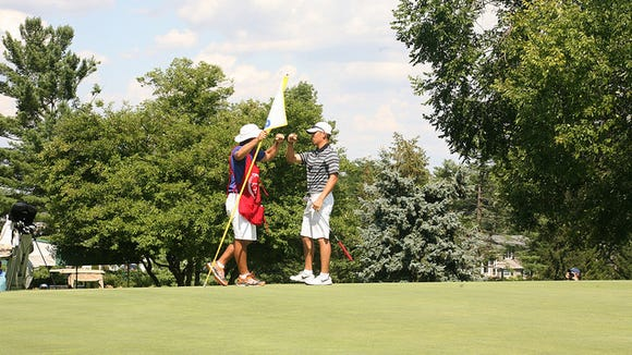 Army junior Peter Kim is congratulated by his caddie