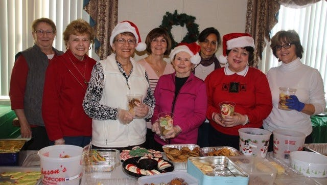 (From left) Millville Woman's Club members Kathy Bennett, Barbara Scudder, Barbara Westog, Lisa Fisher, co-chair of the club's Cookie Project, Sheila Veale, Shelly Goranson, Nuha Hababo and Eda Shannon, co-chair of the club's Cookie Project, prepare containers for the club's annual Cookie Project. The containers are distributed to residents of various residents of senior housing.