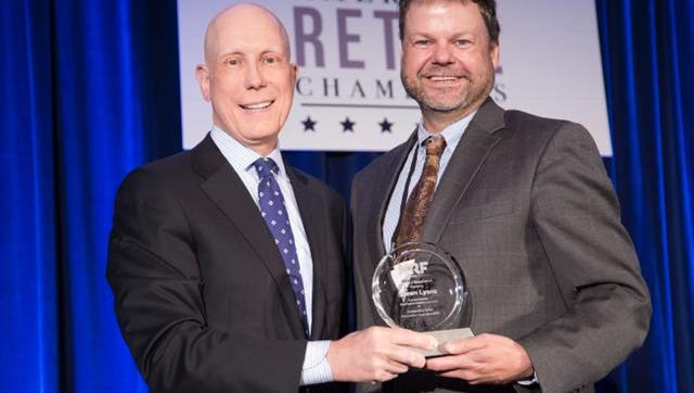 Shawn Lyons, right, accepts the J. Thomas Weyant Award from the National Retail Federation.