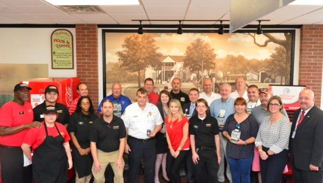 include local first responders, representatives from the Jeffrey Lee Williams Foundation and DHEC, Firehouse Subs Area Representative Shawn Hooks and Firehouse Subs Franchisee Elliott Goldsmith pose for a photo after the presentation regarding the donation of portable carbon monoxide detectors.