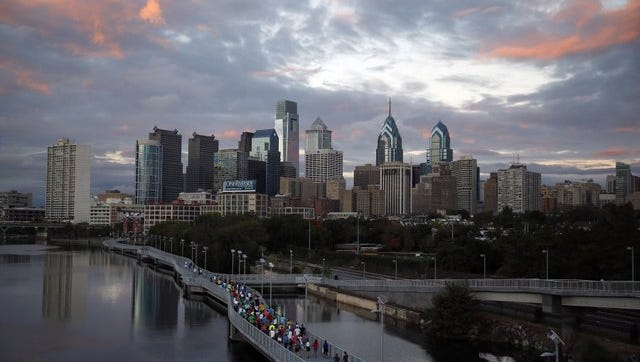 FILE - Runners jog along the Schuylkill Banks Boardwalk, Wednesday, Oct. 1, 2014, in Philadelphia. The city is set to commemorate its newest feature: a 2,000-foot concrete boardwalk overlooking the Schuylkill River. (AP Photo/Matt Slocum)