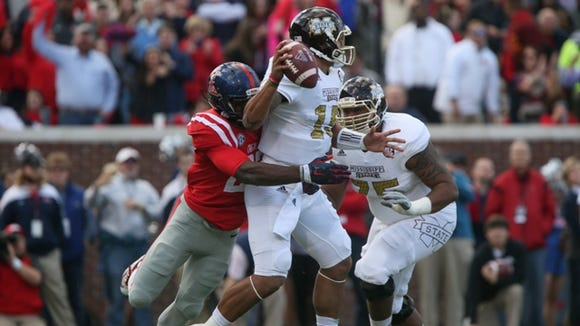 Mississippi State's Dak Prescott (15) is pressured by Ole Miss' Marquis Haynes (27) Mississippi State played Ole Miss in a college football game on Saturday, Nov. 29, 2014 at Vaught-Hemingway  Stadium in Oxford, Miss. (Photo by Keith Warren)