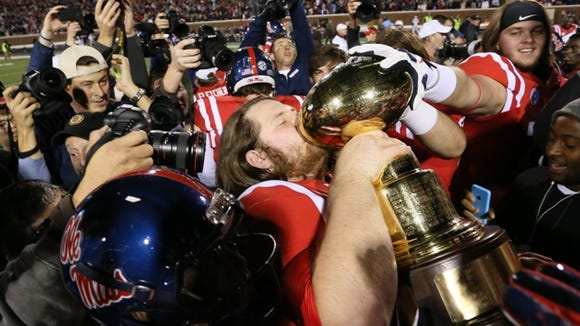 Ole Miss players raise the Egg Bowl trophy after defeating MSU. Mississippi State played Ole Miss in a college football game on Saturday, Nov. 29, 2014 at Vaught-Hemingway  Stadium in Oxford, Miss. (Photo by Keith Warren)