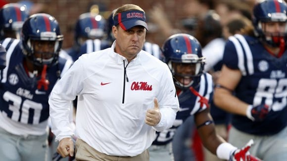 Mississippi coach Hugh Freeze run onto the field before
